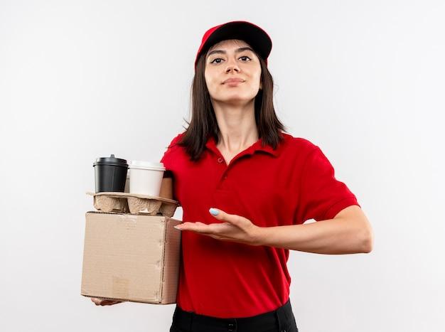 Junges liefermädchen, das rote uniform und kappenhalteboxpaket und kaffeetassen trägt, die mit arm der hand, die sicher steht, über weißer wand stehen