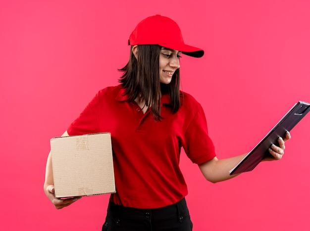 Junges liefermädchen, das rotes poloshirt und kappe hält boxpaket und zwischenablage, die es lächelnd mit glücklichem gesicht über rosa wand stehend betrachten