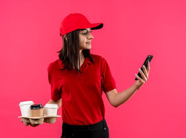 Junges liefermädchen, das rotes poloshirt und kappe hält, die lebensmittelverpackung steht, die über rosa wand steht