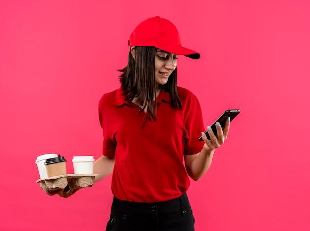 Junges liefermädchen, das rotes poloshirt und kappe hält, die nahrungsmittelpaket betrachten, das ihren smartphonebildschirm lächelnd steht über rosa wand