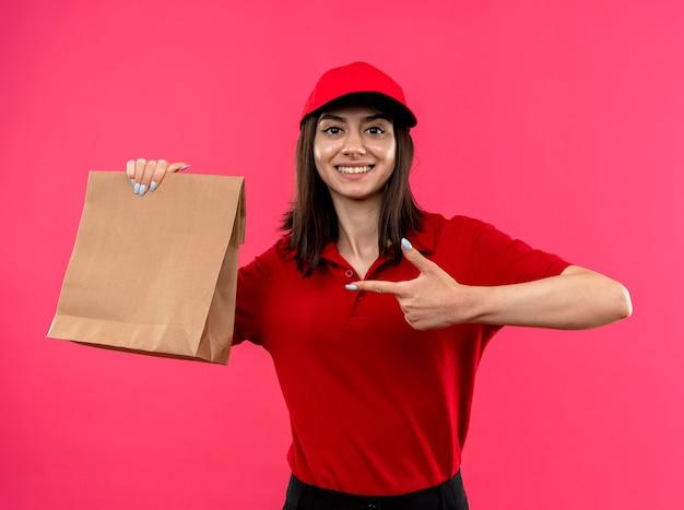 Junges liefermädchen, das rotes poloshirt und kappe hält, die papierpaket hält, das mit zeigefinger darauf zeigt, lächelnd mit glücklichem gesicht, das über rosa wand steht