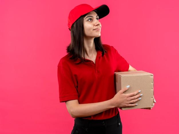 Junges liefermädchen, das rotes poloshirt und kappe hält, die pappkartonpaket hält, das beiseite mit lächeln auf gesicht steht, das über rosa wand steht