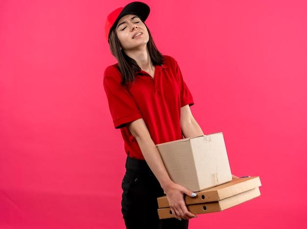 Junges liefermädchen, das rotes poloshirt und kappe hält, die schwere kastenpakete hält, die müde und angespannt stehen über rosa wand stehen