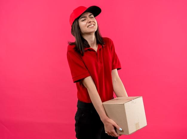 Junges liefermädchen, das rotes poloshirt und kappe hält, die schweres kastenpaket hält, das müde und angespannt steht über rosa wand steht