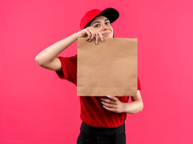 Junges liefermädchen, das rotes poloshirt und kappe hält papierpaket betrachtet kamera mit lächeln auf gesicht steht über rosa hintergrund