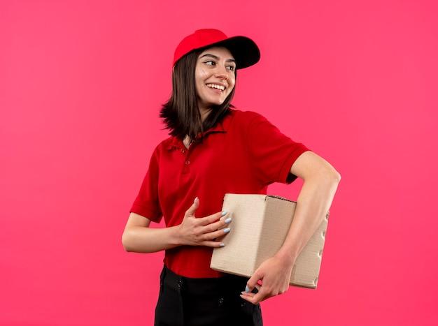 Junges liefermädchen, das rotes poloshirt und kappenhalteboxpaket trägt, das beiseite mit glücklichem lächeln auf gesicht steht über rosa hintergrund steht
