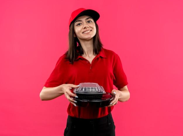 Junges liefermädchen, das rotes poloshirt und mütze hält, die freundliches lächeln lächelnd über rosa wand hält