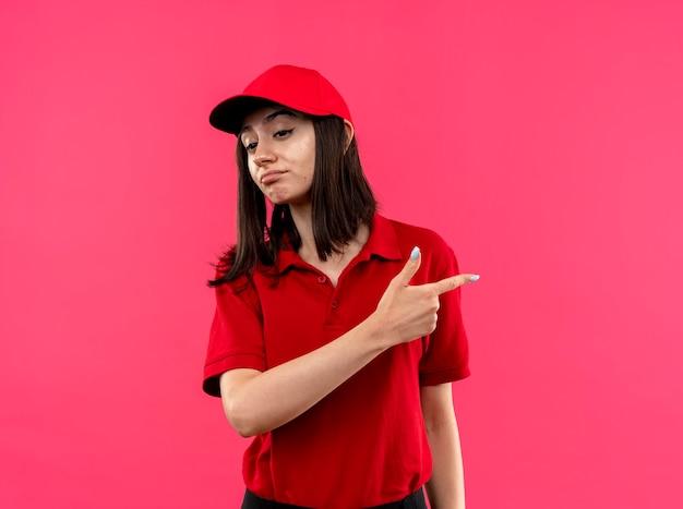 Junges liefermädchen, das rotes poloshirt und mütze trägt, die unzufrieden zeigt, mit zeigefinger zur seite stehend, die über rosa wand steht