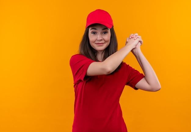 Junges liefermädchen, das rotes t-shirt im lächeln der roten kappe mit handschlag auf lokalisiertem gelbem hintergrund trägt