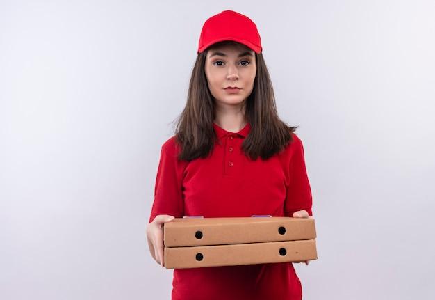 Junges liefermädchen, das rotes t-shirt in der roten kappe trägt, die eine pizzaschachtel auf lokalisiertem weißem hintergrund hält
