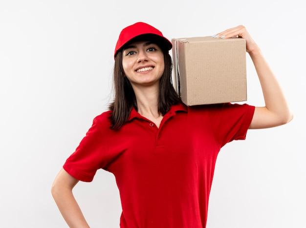 Junges liefermädchen, das rotes uniform- und kappenhalteboxpaket trägt, das mit großem lächeln auf gesicht steht, das über weißem hintergrund steht