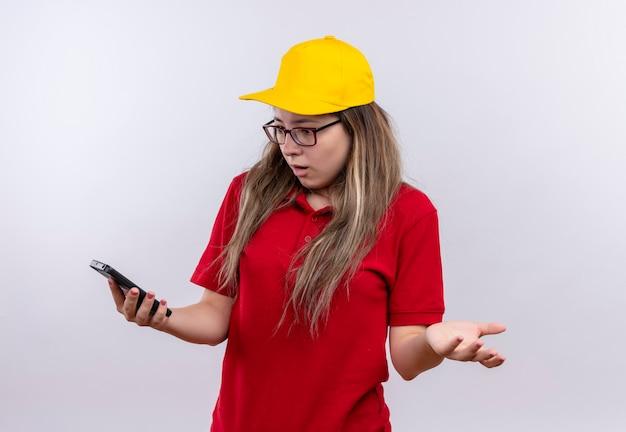 Junges liefermädchen im roten poloshirt und in der gelben kappe, die bildschirm ihres smartphones frustriert betrachten