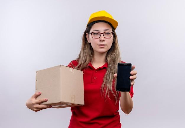 Junges liefermädchen im roten poloshirt und in der gelben kappe, die boxpaket hält, zeigt smartphone, das kamera mit ernstem sicherem ausdruck auf gesicht betrachtet