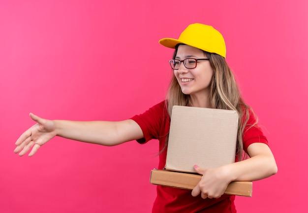Junges liefermädchen im roten poloshirt und in der gelben kappe, die pappkartonsgruß halten, der hand lächelnd anbietet