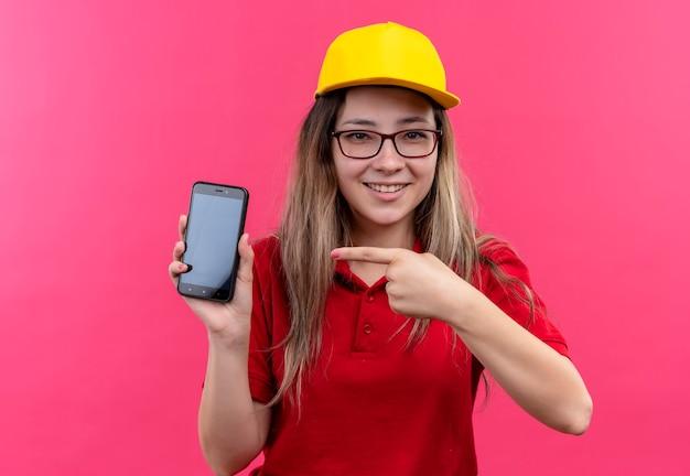 Junges liefermädchen im roten poloshirt und in der gelben kappe, die smartphone zeigt, zeigt mit zeigefinger lächelnd