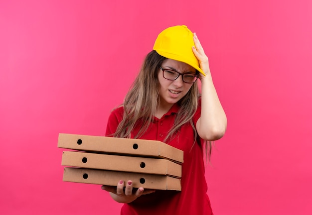 Junges liefermädchen im roten poloshirt und in der gelben kappe, die stapel von pizzaschachteln hält, die verwirrt und sehr besorgt mit hand auf kopf für fehler schauen