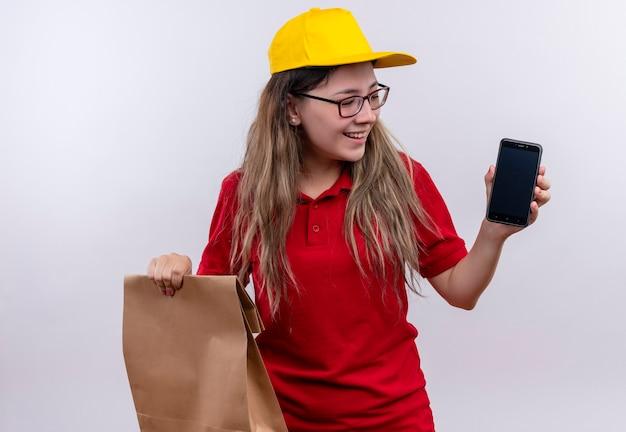Junges liefermädchen im roten poloshirt und in der gelben kappe zeigt smartphone, das papierpaket hält, das fröhlich lächelt