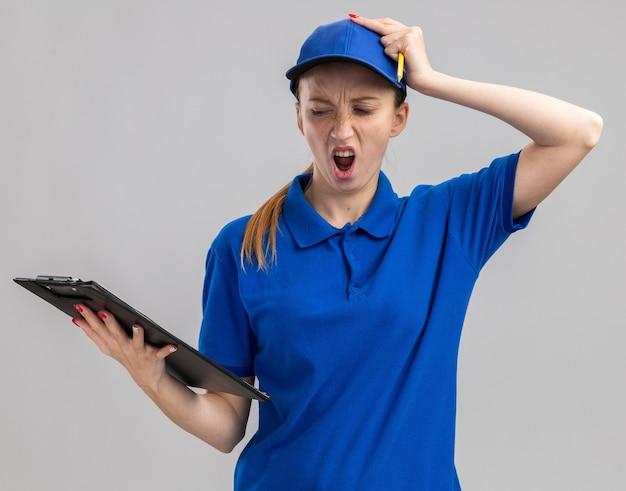 Junges liefermädchen in blauer uniform und mütze, das die zwischenablage hält und es mit der hand auf dem kopf für einen fehler, der über der weißen wand steht, verwechselt sieht