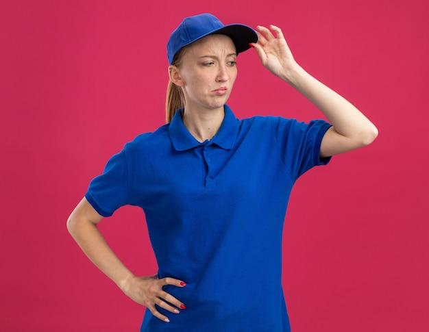 Junges liefermädchen in blauer uniform und mütze, das mit skeptischem ausdruck auf dem gesicht, das die mütze berührt, beiseite schaut