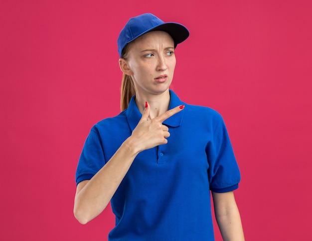 Junges liefermädchen in blauer uniform und mütze, das mit skeptischem ausdruck beiseite schaut und mit dem zeigefinger zur seite zeigt