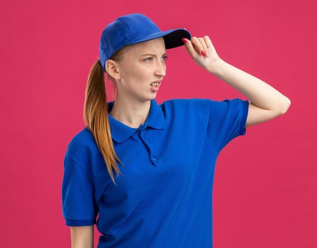 Junges liefermädchen in blauer uniform und mütze, das mit verwirrtem ausdruck mit der hand auf dem kopf beiseite schaut
