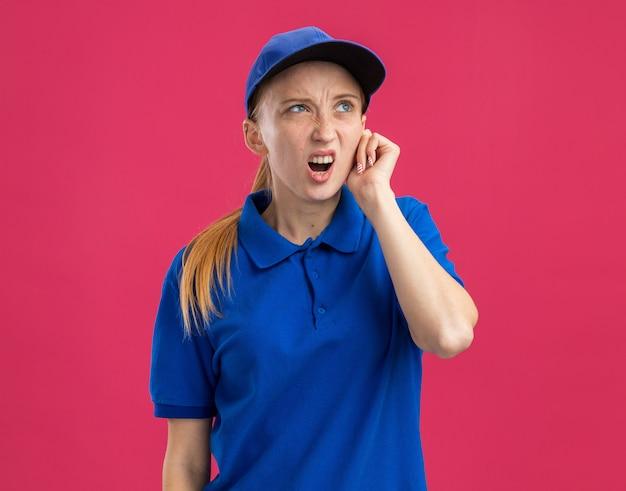 Junges liefermädchen in blauer uniform und mütze, das verwirrt und unzufrieden aufschaut