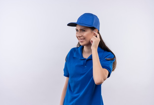 Junges liefermädchen in blauer uniform und mütze, die ohr mit finger mit genervtem ausdruck schließt