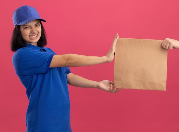 Junges liefermädchen in blauer uniform und mütze, die sich weigert, ein papierpaket zu nehmen, das unzufrieden ist, das über rosa wand steht