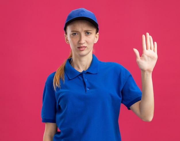 Junges liefermädchen in blauer uniform und mütze mit ernstem, selbstbewusstem ausdruck, der offenen arm zeigt