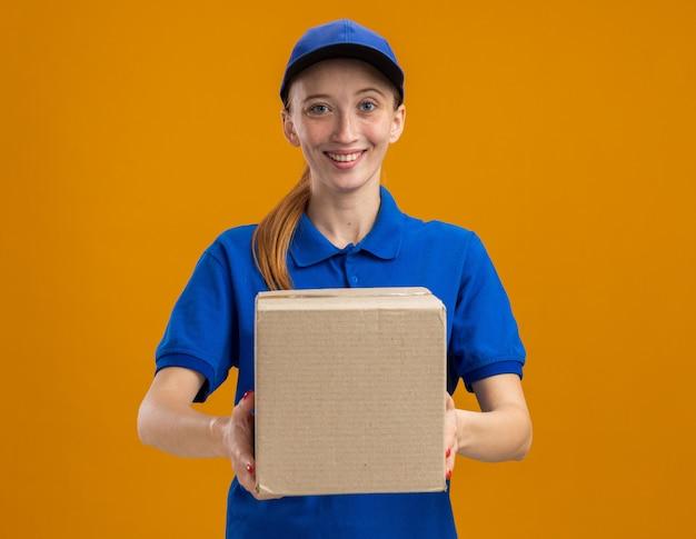 Junges liefermädchen in blauer uniform und mütze mit karton, das zuversichtlich lächelt