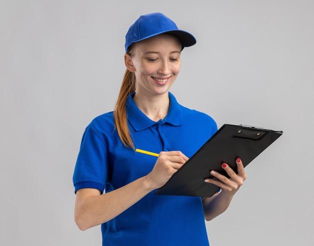 Junges liefermädchen in blauer uniform und mütze mit klemmbrett und bleistift lächelnd selbstbewusst etwas schreiben
