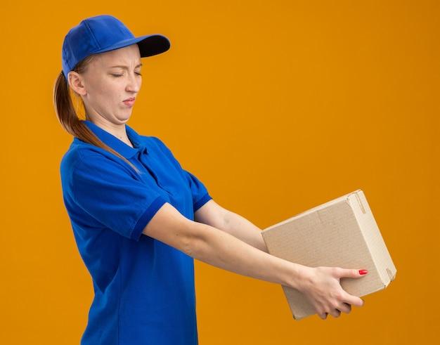 Junges liefermädchen in blauer uniform und mütze mit pappkarton, der es mit angewidertem ausdruck betrachtet, der über oranger wand steht