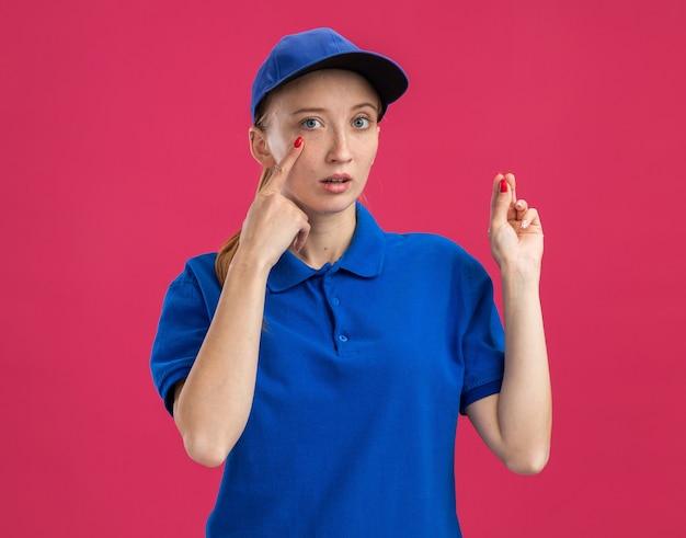 Junges liefermädchen in blauer uniform und mütze überrascht mit zeigefinger auf ihr auge zeigend