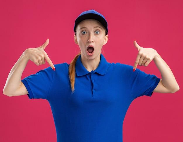 Junges liefermädchen in blauer uniform und mütze überrascht mit zeigefinger nach unten zeigend