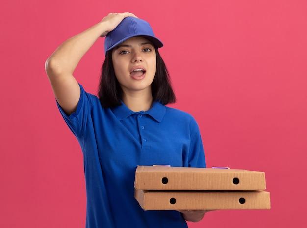 Junges liefermädchen in der blauen uniform, die pizzaschachteln hält, die mit der hand auf ihrem hed für den fehler verwirrt stehen, der über rosa wand steht