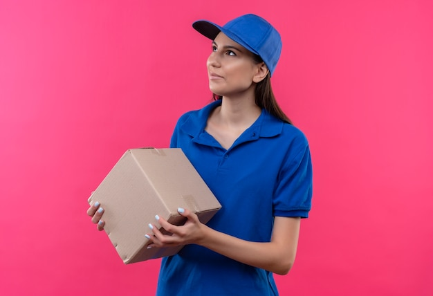 Junges liefermädchen in der blauen uniform und in der kappe, die boxpaket hält, das mit ernstem gesicht beiseite schaut