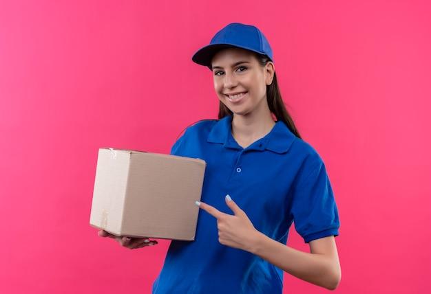 Junges liefermädchen in der blauen uniform und in der kappe, die boxpaket hält, zeigt mit dem finger fröhlich samiling