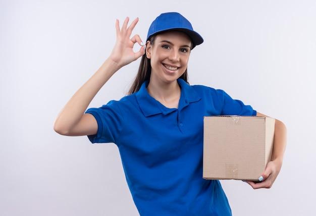 Junges liefermädchen in der blauen uniform und in der kappe, die boxpaket lächelnd zuversichtlich zeigt, ok zeichen zeigend