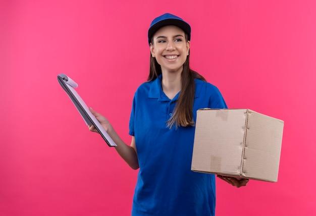 Junges liefermädchen in der blauen uniform und in der kappe, die boxpaket und zwischenablage hält, die mit lächeln auf gesicht beiseite schauen