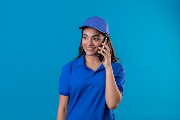 Junges liefermädchen in der blauen uniform und in der kappe, die das lächelnde freundliche sprechen auf handy über blauem hintergrund beiseite schauend schaut