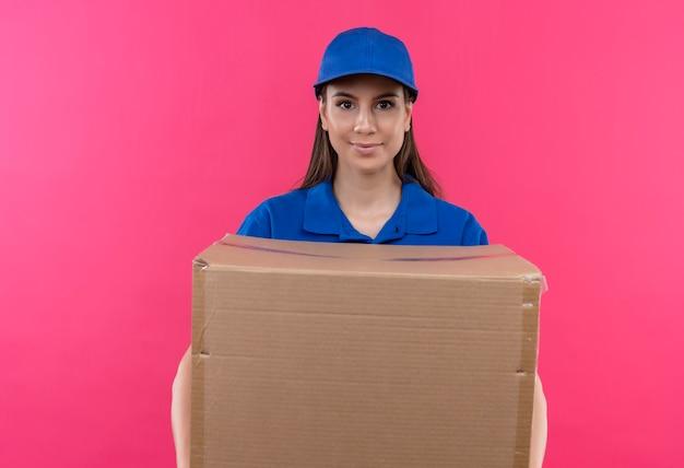 Junges liefermädchen in der blauen uniform und in der kappe, die großes kastenpaket betrachten kamera mit ernstem selbstbewusstem ausdruck betrachten