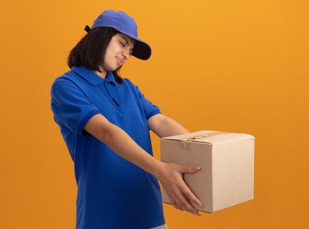 Junges liefermädchen in der blauen uniform und in der kappe, die karton hält, der es mit angewidertem ausdruck betrachtet, der über orange wand steht