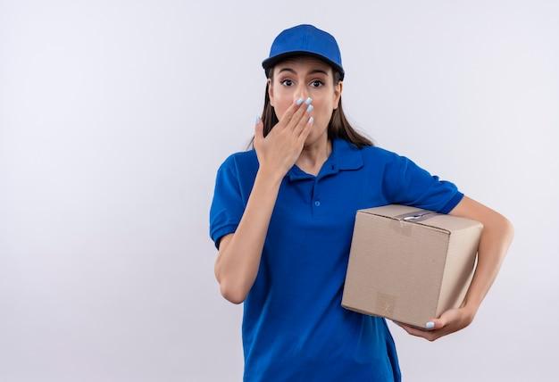 Junges liefermädchen in der blauen uniform und in der kappe, die kastenpaket schockierte, bedeckte mund mit hand