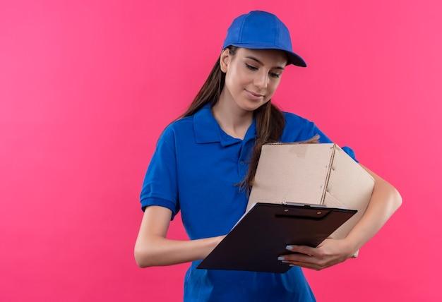 Junges liefermädchen in der blauen uniform und in der kappe, die kastenpaket und zwischenablage hält, die leere seiten mit ernstem gesicht betrachten
