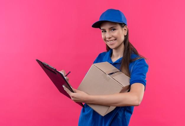 Junges liefermädchen in der blauen uniform und in der kappe, die kastenpaket und zwischenablage hält, die zuversichtlich lächeln