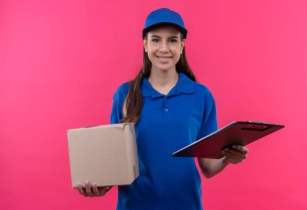 Junges liefermädchen in der blauen uniform und in der kappe, die kastenpaket und zwischenablage hält, die zuversichtlich schauen
