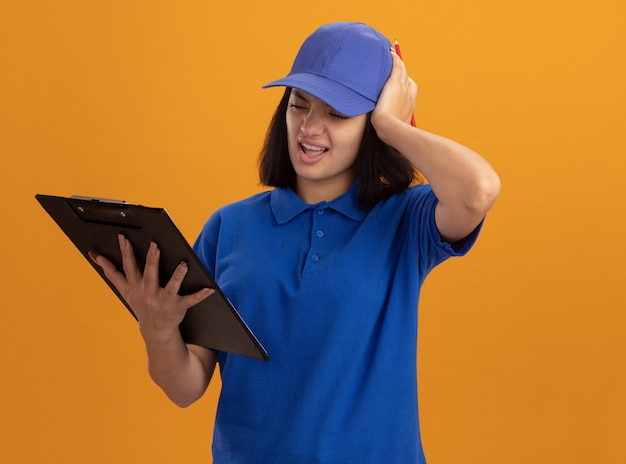Junges liefermädchen in der blauen uniform und in der kappe, die klemmbrett hält, das mit hand auf ihrem kopf für fehler verwechselt betrachtet, der über orange wand steht