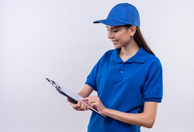 Junges liefermädchen in der blauen uniform und in der kappe, die leere seiten in der zwischenablage mit lächeln auf gesicht betrachten