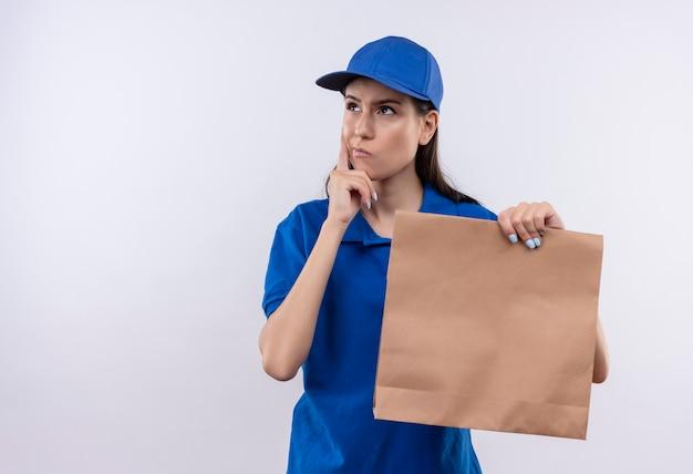 Junges liefermädchen in der blauen uniform und in der kappe, die papierpaket hält, das mit nachdenklichem ausdruck auf gesicht beiseite schaut und denkt