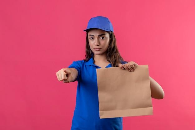 Junges liefermädchen in der blauen uniform und in der kappe, die papierpaket hält, zeigt mit dem finger zur kamera unzufrieden, die über rosa hintergrund steht